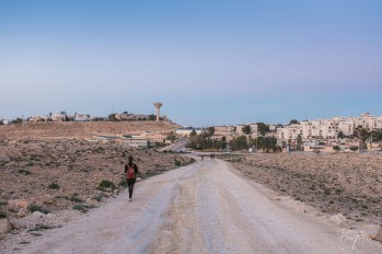 A girl is walking down a dusty path in Mitzpe Ramon at sunset