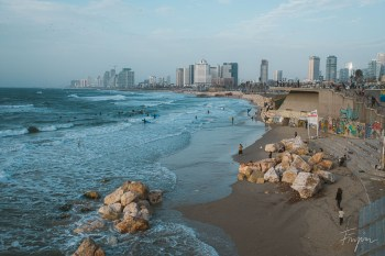 Beachfront of Tel Aviv with skyscrapers in the background and surfing people in the water