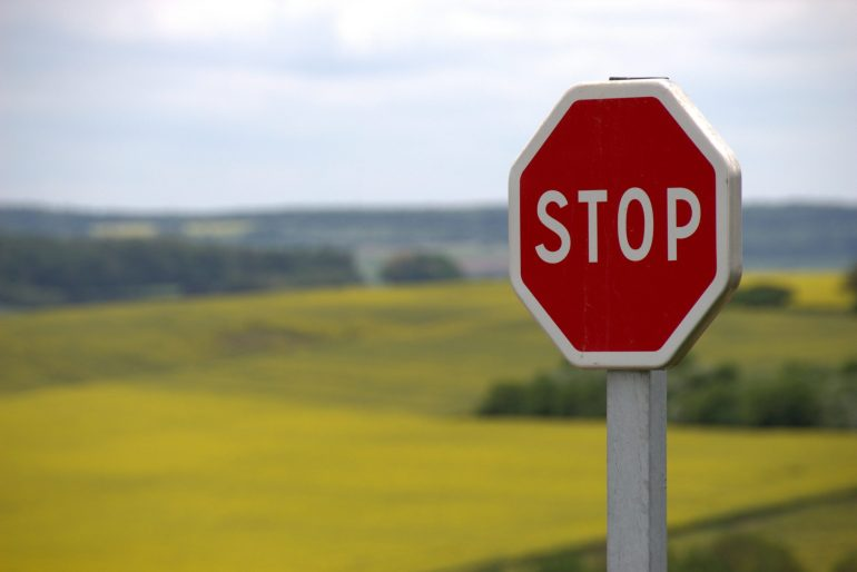 red stop sign in front of a field