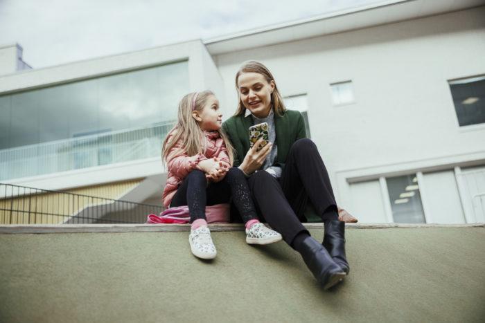 امرأة وفتاة تجلسان في الخارج أمام مبنى مدرسة، وتنظران إلى هاتف محمول تحمله المرأة.