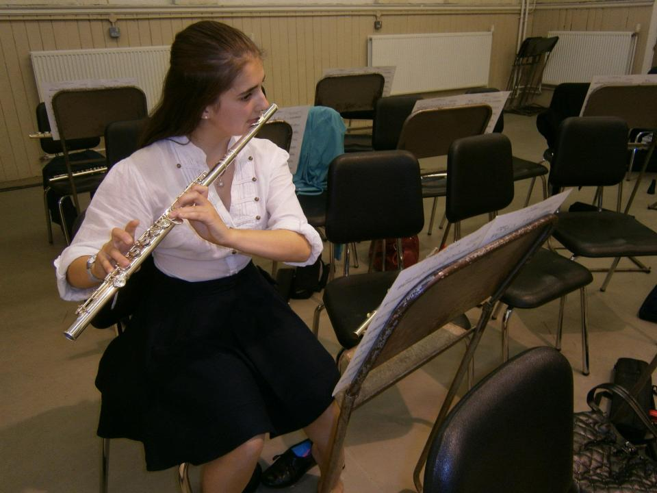 A photo of me with long dark hair, playing the flute in a mostly-empty band room.