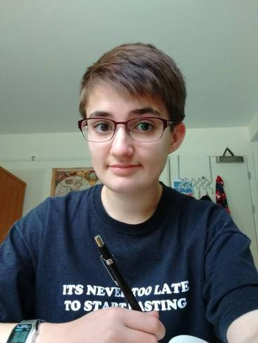 A selfie of me holding a pencil, with short hair and glasses.