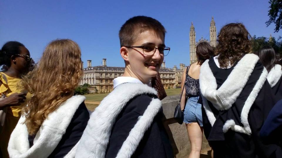 A photo of me looking back over my shoulder, wearing a gown and hood, with King's College Chapel in the background.
