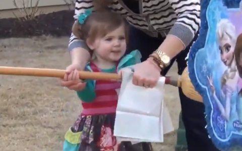 Madre del año ayudando a su hija a romper una piñata