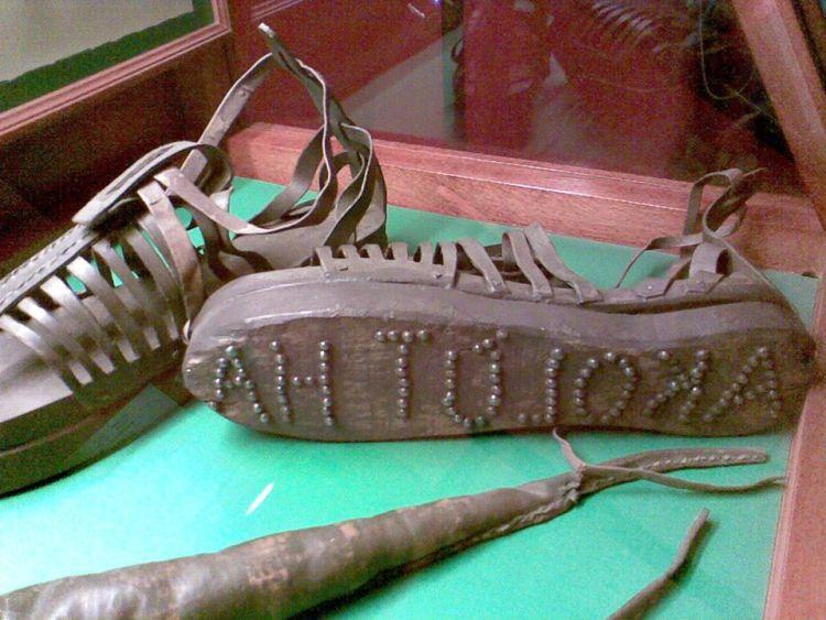 """Sandalias de una prostitvta de la antigua Grecia con la inscripción """"Sigueme"""" para que quedara marcada en la arena."""
