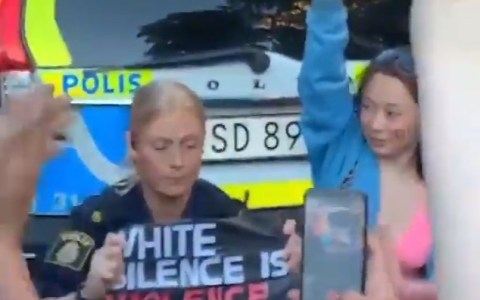Una policía se arrodilla en Suecia, sosteniendo un cartel para mostrar su apoyo a los negros, y se pone a llorar.