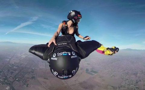 Una mujer cabalgando un paracaidista con wingsuit
