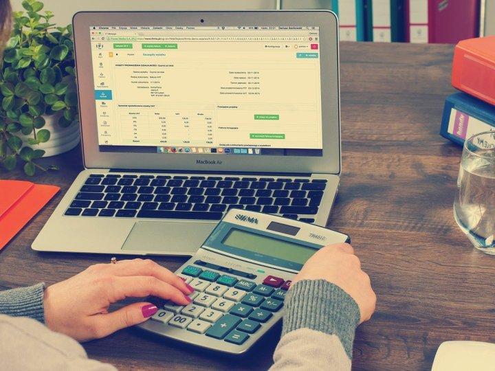 notebook em cima da mesa e uma pessoa usando calculadora