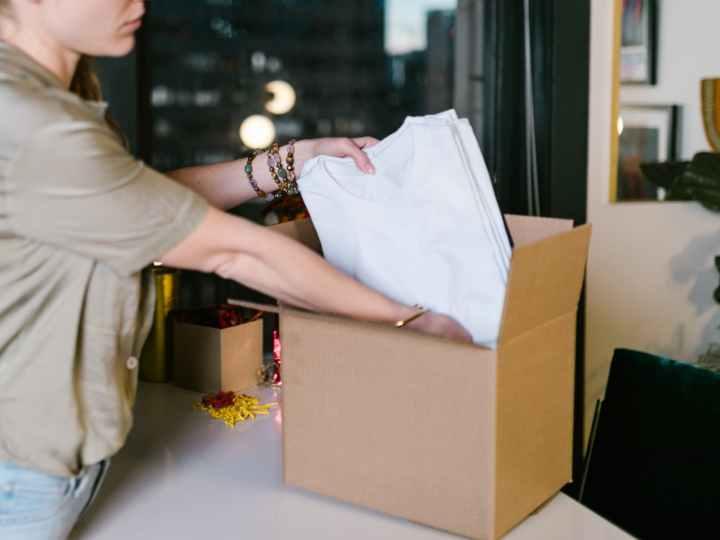 woman putting t shirts into box