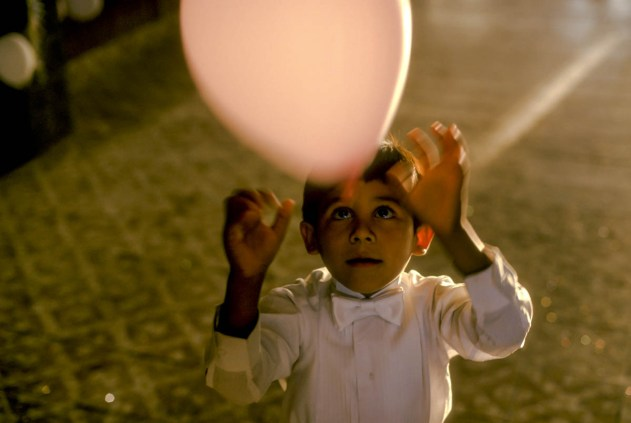 A young boy chases a balloon at a Quinceañera in Arizona.