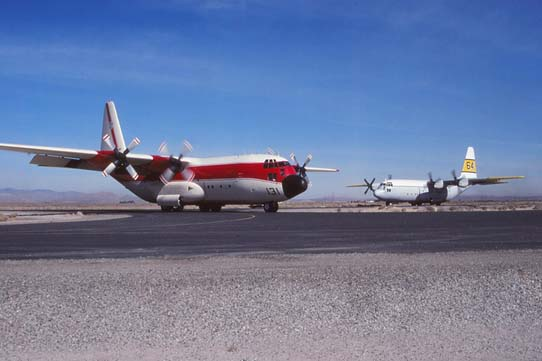 Two Lockheed C130's, Tankers 131 and 64, taxi into the ramp at Fox Field Air Attack Base.