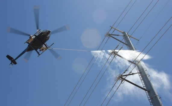 helicopter pressure washes a power line