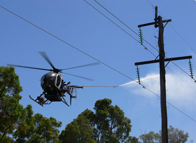 A helicopter in Western Australia pressure washes a power line in this file photo  from Western Power.