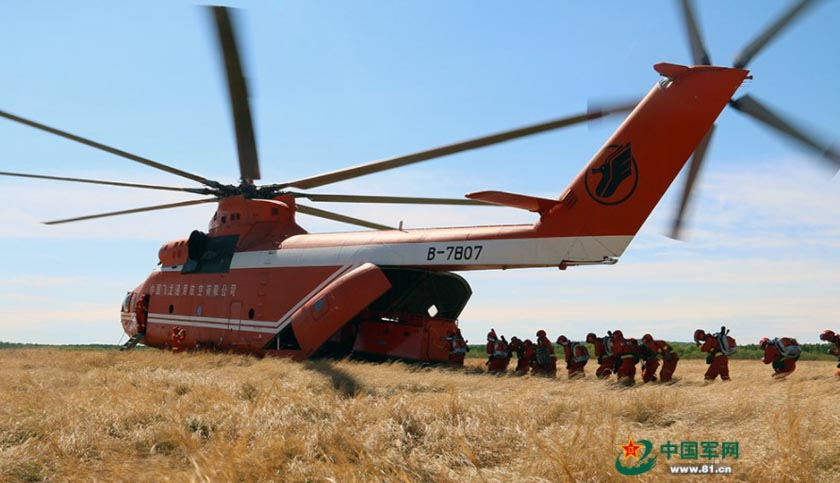 Armed forest officers and soldiers in China work with Mi-26 helicopter