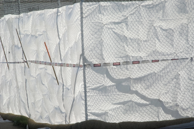 asbestos tape on the white plastic fence