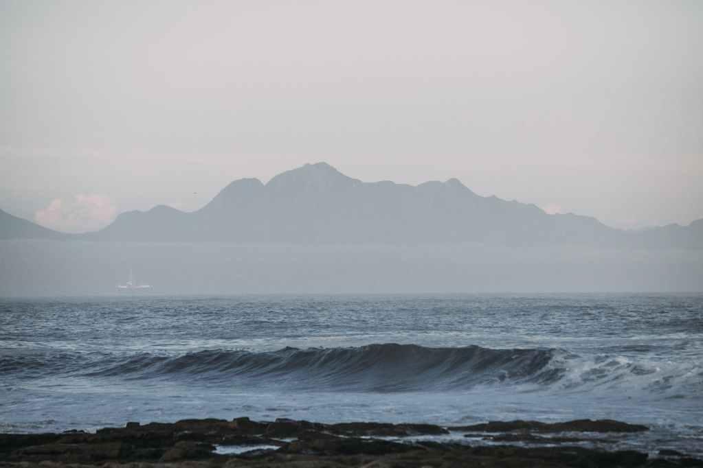 coastline near waving blue sea against misty mountains