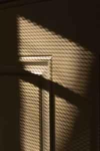 beige wall with window net shadows