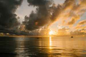 ocean with boats under cloudy sky at sundown