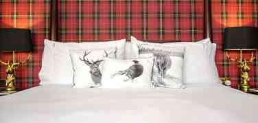 Tartan wallpaper sits behind a four poster bed made up with black and white cushions with pictures of a stag, a pheasant and a Highland cow