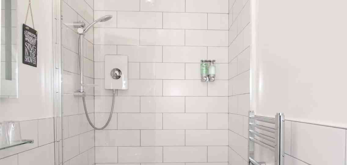 White bathroom with white tiles, walk in shower and full height glass shower screen