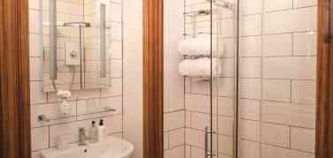Shower stall with clear glass doors leading into white and oak bathroom in the Hare room in Firhall Highland Bed & Breakfast
