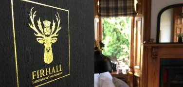 Guest information folder in the foreground with the Hare bedroom at Firhall Highland B&B in the background