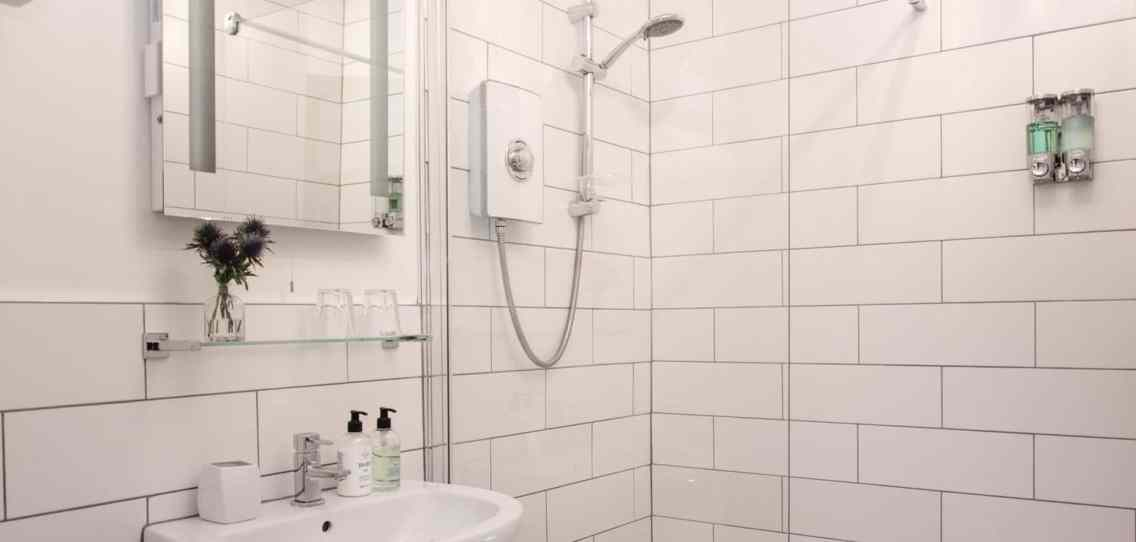 White tiled bathroom with a white sink above which there is a glass shelf with local thistles in a vase