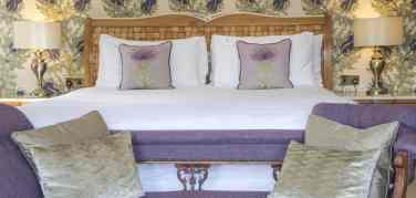 Looking onto the bed in the Spey Room in Firhall Bed & Breakfast with intricate thistle wallpaper and gold and purple cushions