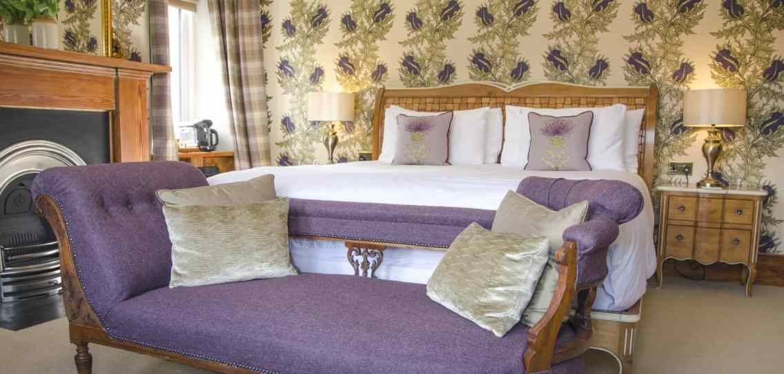 Wide view of the Spey bedroom at Firhall B&B showing the purple chaise lounge at the end of the bed