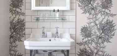 large white sink in a bathroom with glass shelf and white tiles behind flanked by black and white large pattern thistle wallpaper