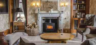High backed chairs and a low Harris Tweed sofa in front of a wood burning stove in the guest lounge at Firhall B&B