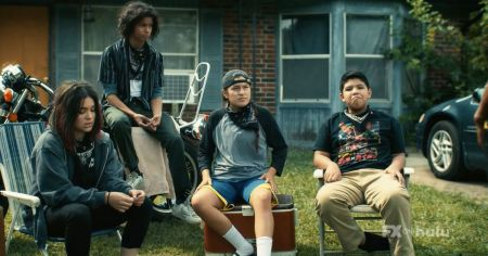 Four native teens hanging out in front of their house