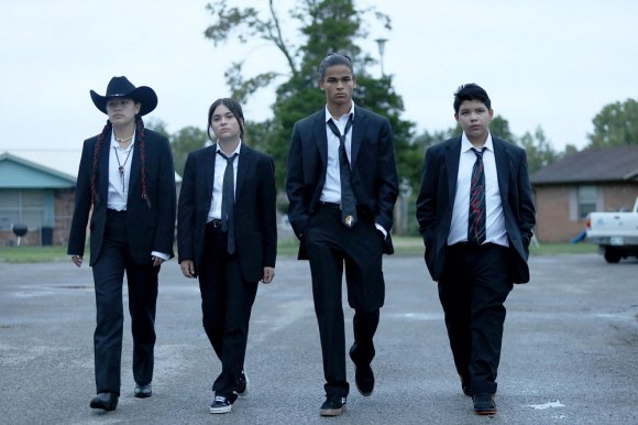 Four native youth, stars of Reservation Dogs, in black suits with black ties walking across parking log