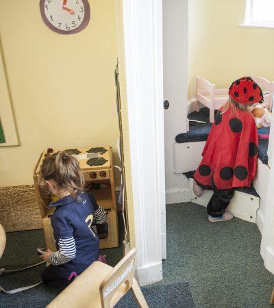 2 children playing in house corner