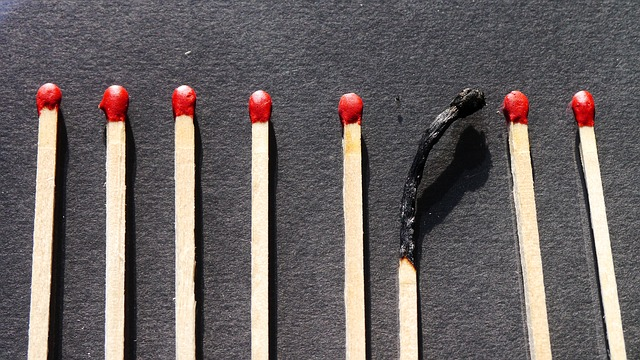 One burned match among other unlit matches