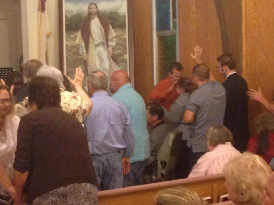 Group of people praying at the altar