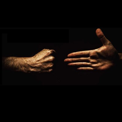 An open hand meeting a closed fist