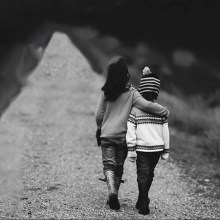 Two young girls walking arm in arm