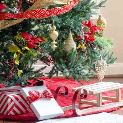 Christmas gifts under red and gold Christmas tree