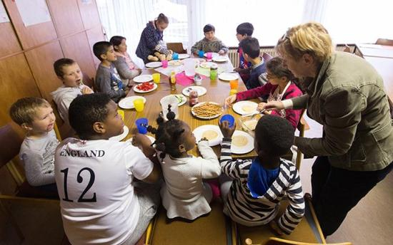 A volunteer serves a meal to immigrant children in Germany.