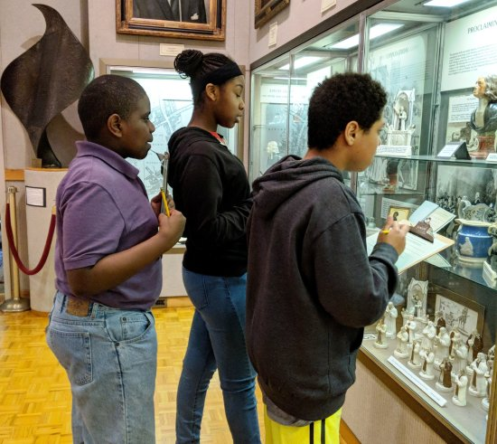 Youth examine historic Methodist artifacts in a display case.