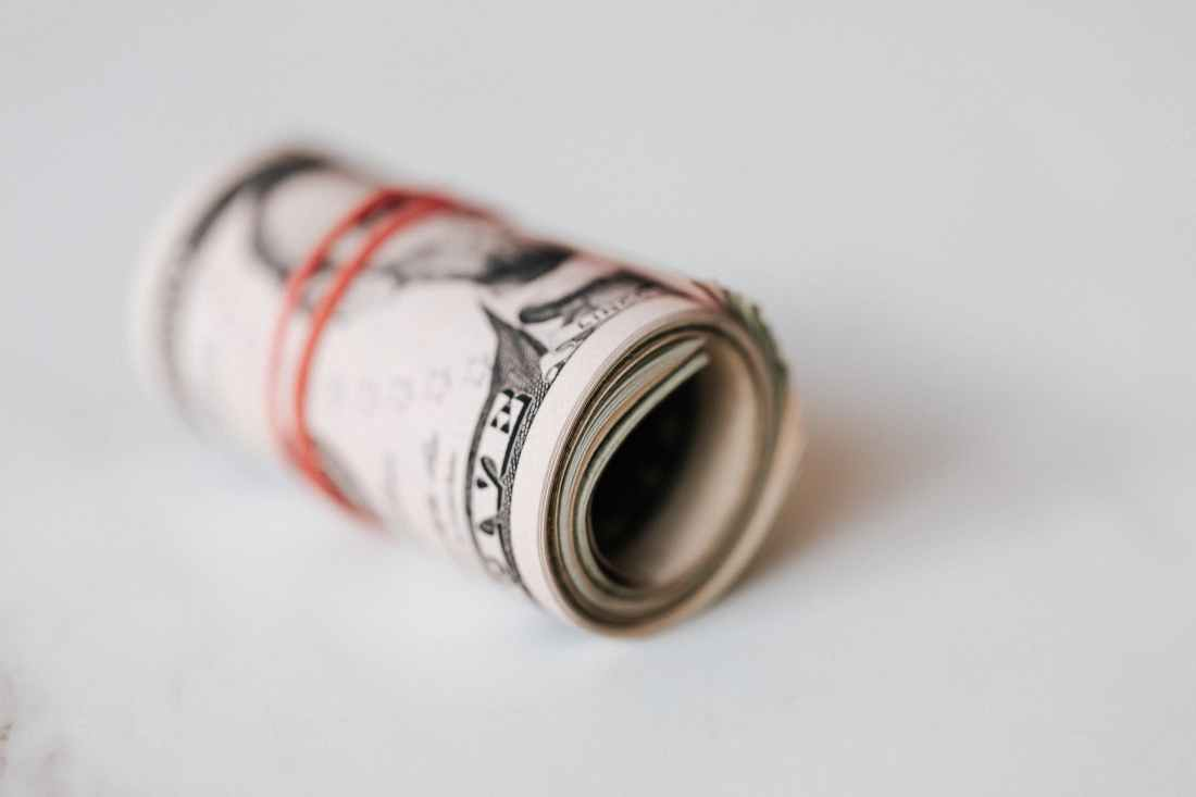 rolled dollars placed on white surface