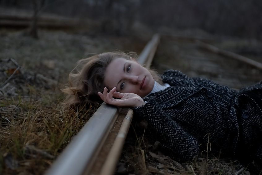 Woman laying hear on railroad track