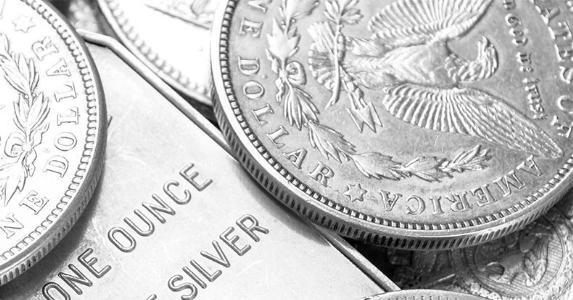 Close up of Morgan Silver Dollars, Silver Eagles, and Silver Bars