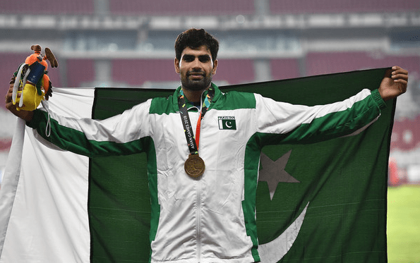 Arshad Nadeem is standing with the flag