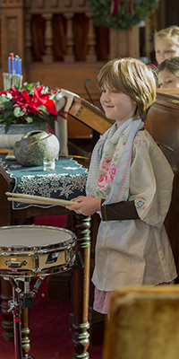 Child playing the drums at a First Parish service