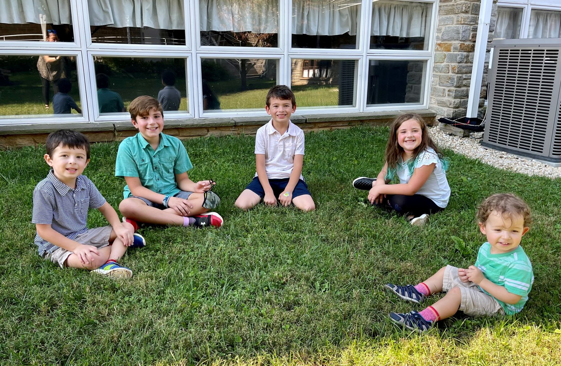 5 children sitting on the grass smiling