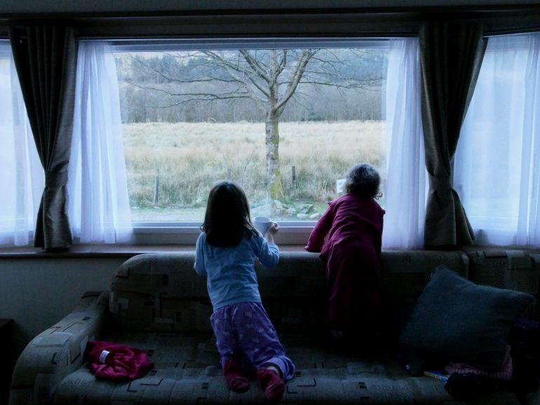 enfants devant une fenetre dans un mobil-home dans le Glen Coe (Ecosse)
