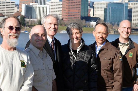 """ODFW biologists Paul Scheerer (left) and Brian Bangs (right) on the Willamette Esplanade with Oregon Gov. John Kitzhaber, U.S. Interior Secretary Sally Jewell, and Chris Allen, U.S. Fish and Wildlife Service biologist, and Rollie White, U.S. Fish and Wildlife Service deputy state supervisor. The photo op took place following the announcement that the Oregon chub is the first fish in the United States to achieve """"recovered"""" status under the Endangered Species Act. (Photo by Rick Swart)"""