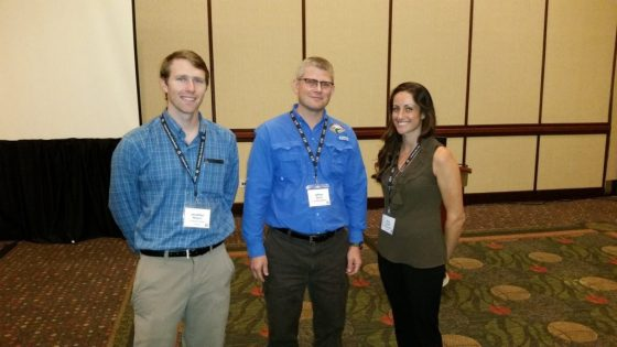 Student travel award winners Jonathan Watson (left) and Amy Cottrell (right) with symposium organizer Jeff Quinn (center). Photo Credit: Michael Siepker